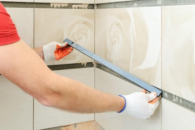 Instalação do friso na parede. um trabalhador colocando ladrilhos no banheiro.