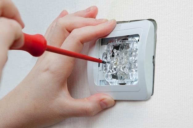 Instalação do interruptor de luz de parede do vestiário com chave de fenda.
