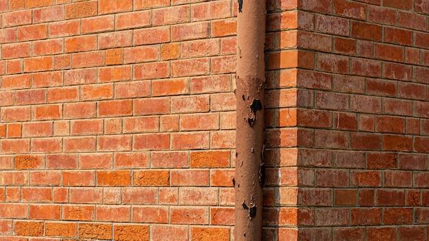 Instalação do sistema de tubulação de água na parede de tijolos laranja