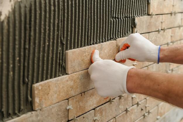 Instalação dos ladrilhos na parede. um trabalhador colocando telhas em forma de tijolo.