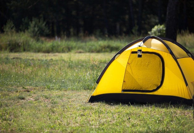 Instalada barraca turística e lanterna de acampamento na natureza na floresta. turismo doméstico, férias ativas de verão, aventuras em família. ecoturismo, distância social. copie o espaço