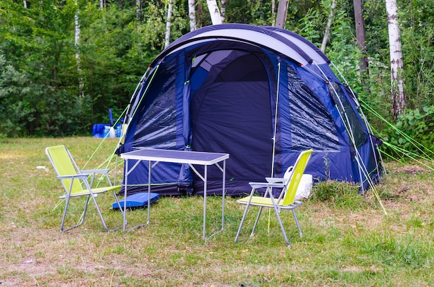 Instalada mesa e cadeiras de acampamento para tenda turística azul na floresta no acampamento