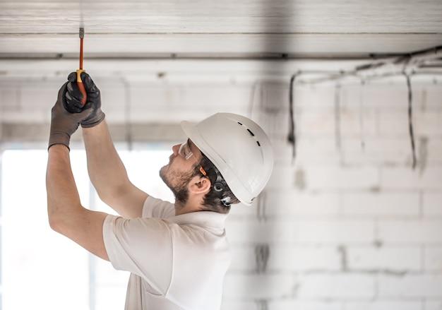 Instalador eletricista com uma ferramenta nas mãos, trabalhando com cabo no canteiro de obras