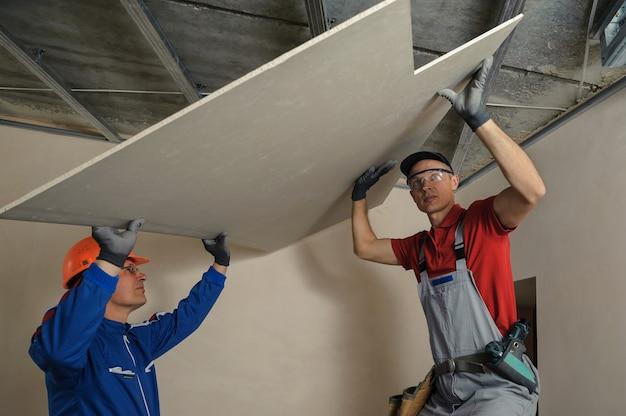 Instaladores de drywall. homens segurando uma placa de gesso descobriram corte