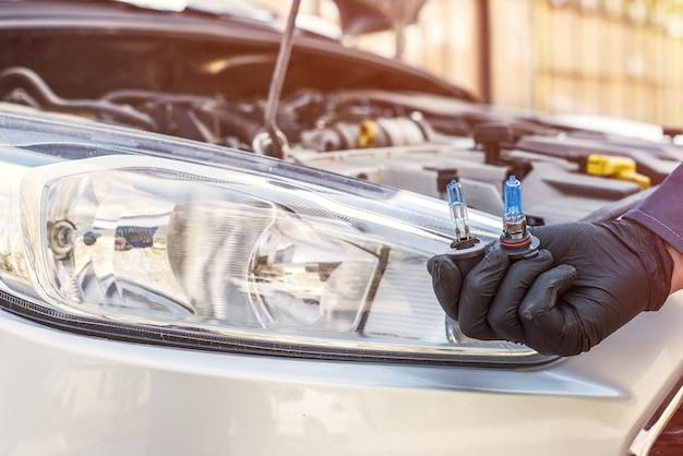 Instalando a nova lâmpada de halogênio moderna do farol do carro