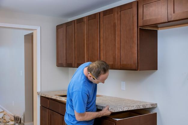 Instalando empreiteiros um tampo laminado de uma remodelação da cozinha.