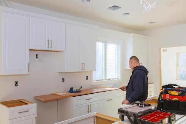 Instalando novo no armário moderno de cozinha.