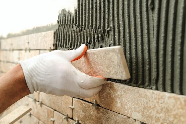 Instalando os azulejos na parede.