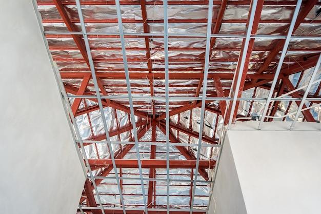 Instale a estrutura de metal para o teto de placa de gesso na casa em construção