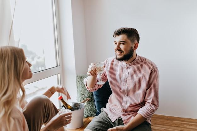 Instantâneo de casal apaixonado, desfrutando de champanhe. homem com barba olha suavemente para a namorada.