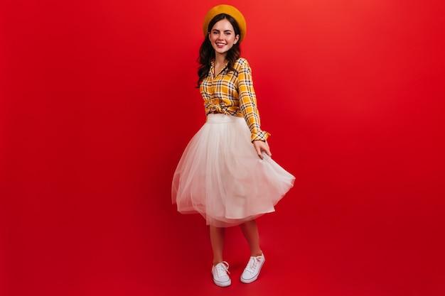 Instantâneo de corpo inteiro de uma garota de cabelos escuros encaracolados em roupa brilhante. mulher de boina e saia fofa está girando na parede vermelha.