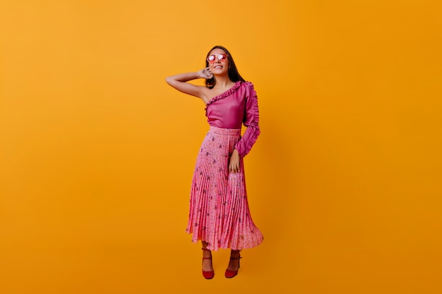 Instantâneo de corpo inteiro na sala laranja na parede isolada. mulher bem feita em top rosa e saia maxi coquete tocando seu pescoço