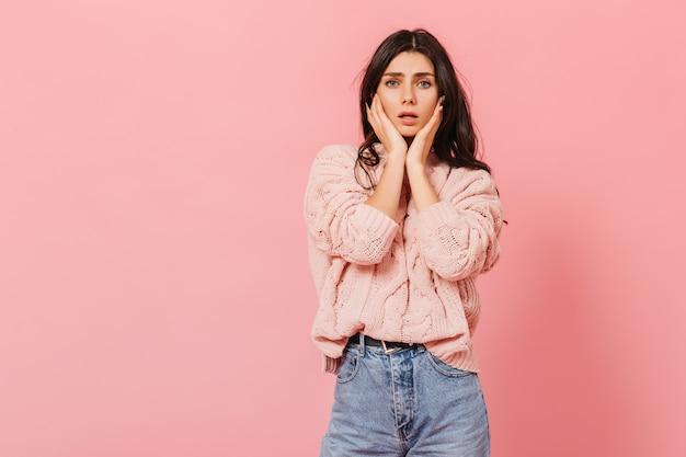 Instantâneo de dolorosa garota de cabelos escuros em estúdio rosa. mulher na camisola de malha, tristemente, olha para a câmera.