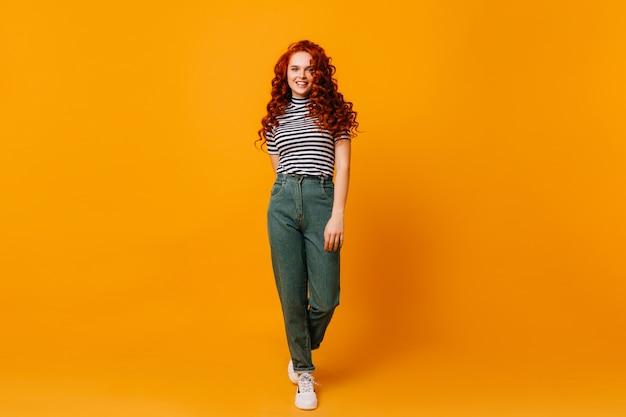 Instantâneo de mulher ruiva em calças jeans. garota de ótimo humor se move no espaço isolado laranja.