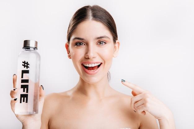 Instantâneo do modelo sorridente atraente na parede branca. menina sem maquiagem aponta para a garrafa, demonstrando que água é vida.