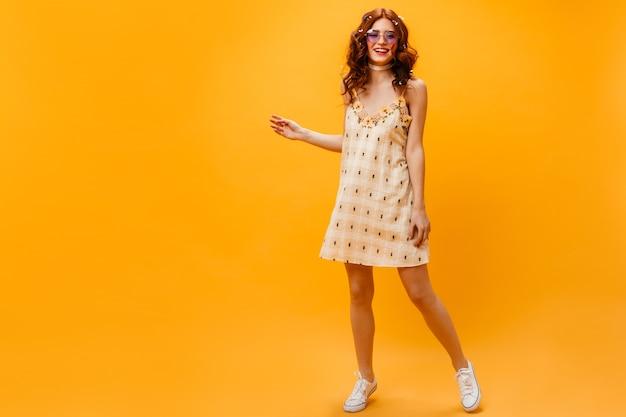 Instantâneo em pleno crescimento de jovem magro em vestido amarelo curto. mulher ruiva em óculos de sol posando em fundo laranja.