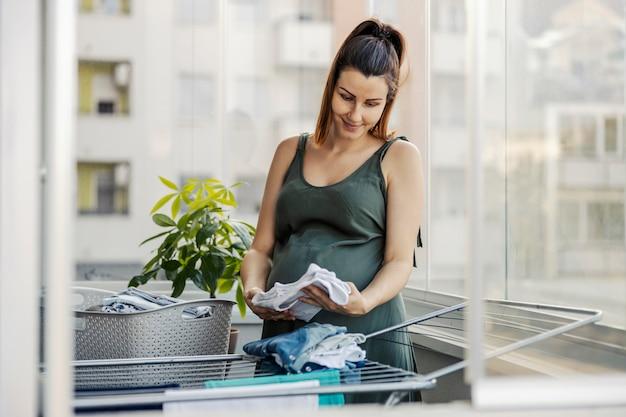 Instinto materno, tarefas domésticas e gestantes. uma animada futura mãe prepara roupas para o recém-nascido. uma mulher grávida está no terraço preparando roupas para o recém-nascido