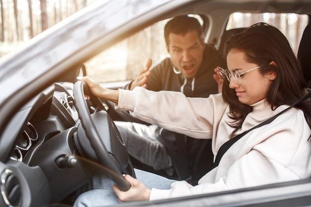 Instruções de condução. uma jovem aprende a dirigir pela primeira vez. ela não funciona bem. o marido ou o instrutor grita com ela. ela está chorando