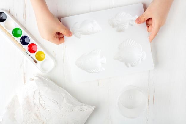 Instruções passo a passo: como fazer figuras de gesso. o conceito de bricolage. ingridients para fazer baixos-relevos em ímãs. etapa 2 preparação para fazer moldagem de gesso, ingredientes nas mãos de criança