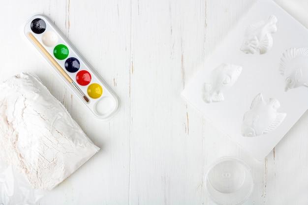 Instruções passo a passo: como fazer moldagem de gesso (figuras). conceito de bricolage e criatividade infantil. etapa 2: ingredientes e ferramentas de preparação para fazer baixos-relevos em ímãs.