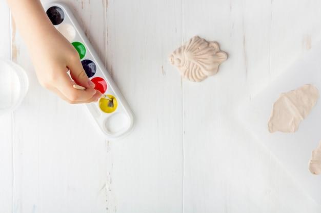 Instruções passo a passo: como fazer moldagem de gesso (figuras). conceito de bricolage e criatividade infantil. fazendo baixos-relevos em ímãs. etapa 7 colorindo a figura do peixe acabado com tintas