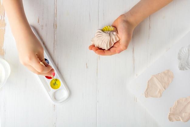Instruções passo a passo: como fazer moldagem de gesso (figuras). conceito de bricolage e criatividade infantil. fazendo baixos-relevos em ímãs. passo 7 colorindo a figura de peixe acabado com tintas de criança