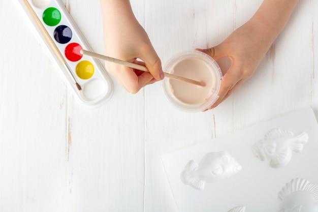 Instruções passo a passo como fazer moldagem de gesso (figuras). conceito de bricolage e criatividade infantil. fazendo baixos-relevos em ímãs. passo 7 processo de mistura de gesso em pó com água por criança