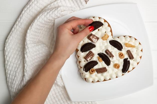 Instruções passo a passo da receita do bolo em forma de coração. etapa 12: decore o bolo com gotas de chocolate, waffles e biscoitos. postura plana.