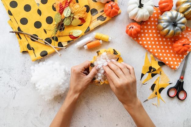 Instruções passo a passo de fazer artesanato de abóbora diy têxtil de halloween. etapa 4 - encher o tecido com um recheio. vista superior plana lay