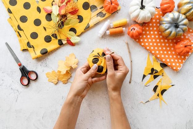 Instruções passo a passo de fazer artesanato de abóbora diy têxtil de halloween. etapa 5 - coloque uma vara no meio. vista superior plana lay
