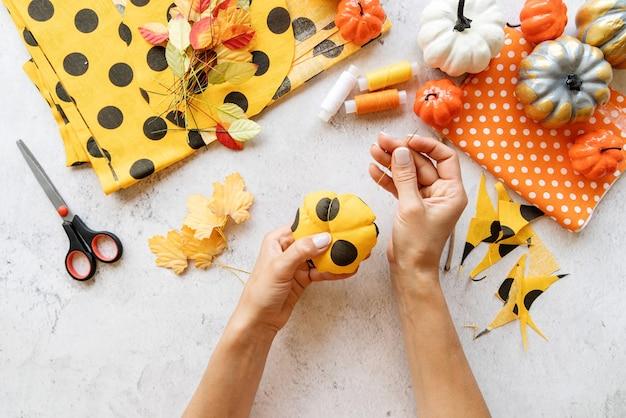 Instruções passo a passo de fazer artesanato de abóbora diy têxtil de halloween. passo 6 - use a agulha e a linha para dividir a abóbora em seções. vista superior plana lay