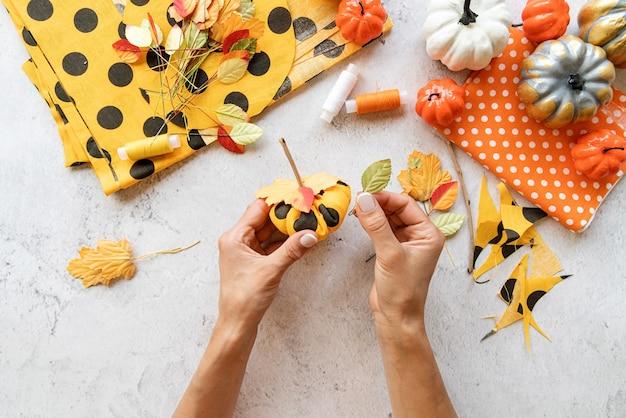Instruções passo a passo de fazer artesanato de abóbora diy têxtil de halloween. passo 7 - decore o topo da abóbora com folhas de outono. vista superior plana lay