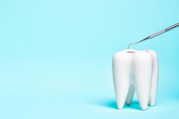 Instrumento de sonda de explorador dental com modelo de dente branco sobre fundo azul claro.