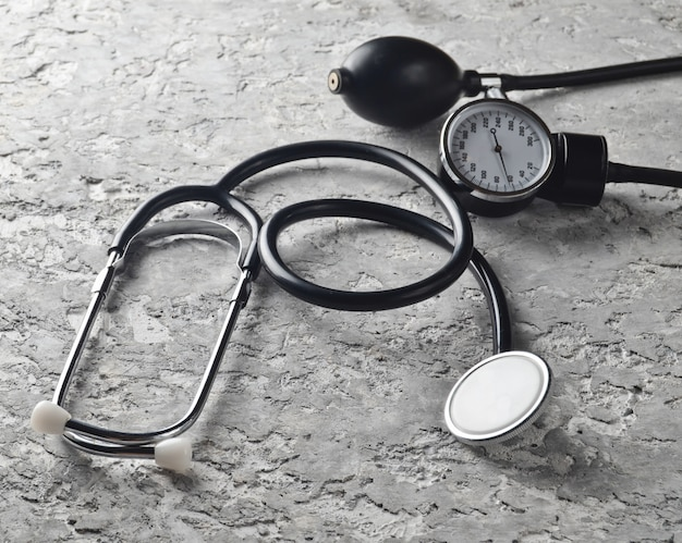 Instrumento médico para medir a pressão. estetoscópio em uma mesa de concreta cinza. diagnóstico cardiovascular.
