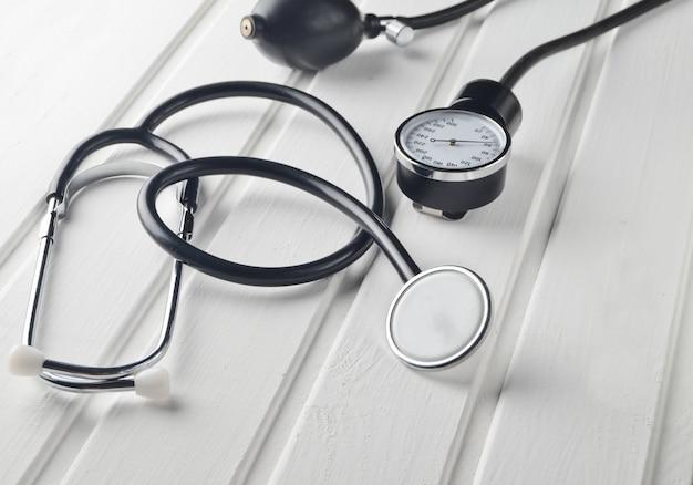 Instrumento médico para medir a pressão. estetoscópio em uma mesa de madeira branca. diagnóstico cardiovascular.