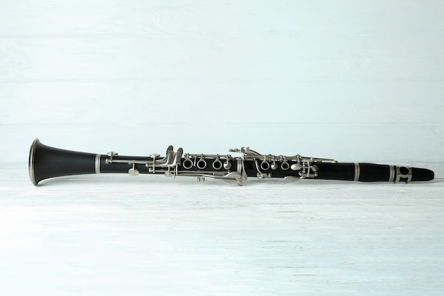 Instrumento musical de clarinete em fundo branco de madeira.