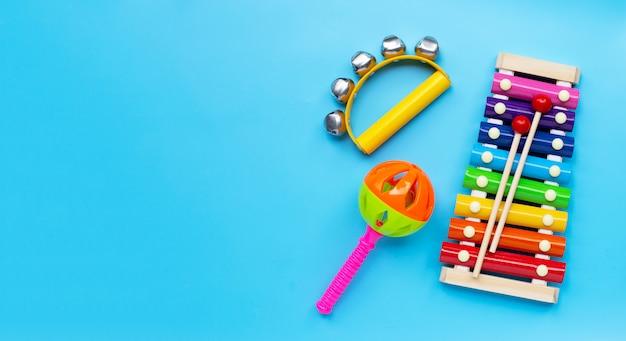 Instrumento musical de sinos de mão para tocar com xilofone colorido e chocalho de bebê sobre fundo azul.