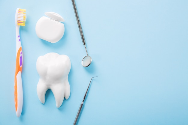Instrumento odontológico de aço profissional com um espelho perto do modelo de dente branco, escova de dentes e fio dental na mesa azul clara