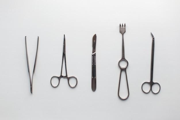 Instrumentos cirúrgicos em uma mesa branca.