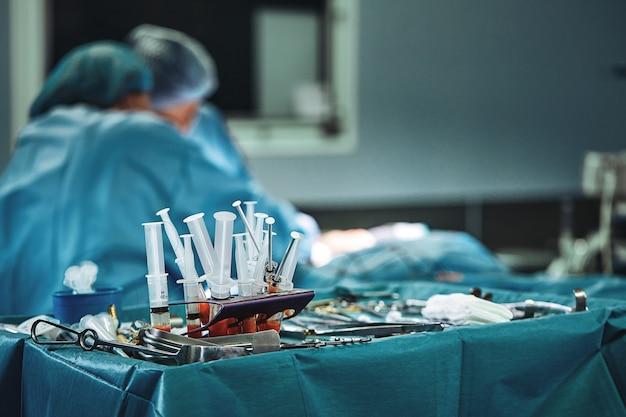 Instrumentos cirúrgicos na sala de operação, dispostos sobre uma mesa esterilizada em um tecido especial azul. t