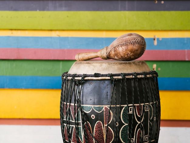 Instrumentos de percussão ao lado da parede de listras multicoloridas com espaço para texto