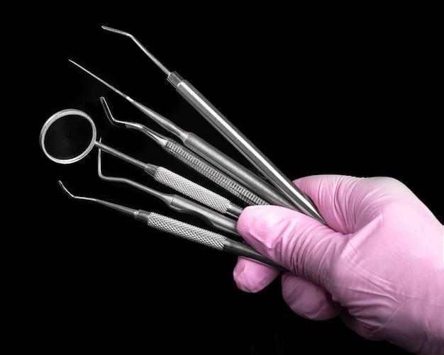 Instrumentos dentais na mão na luva rosa no preto. higiene de clínica dentária