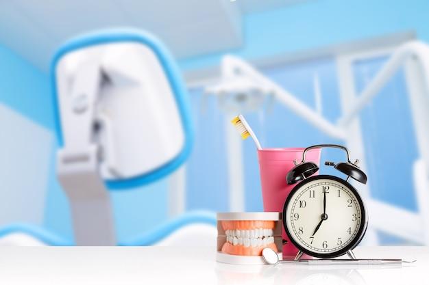 Instrumentos dentais perto de mandíbula humana, despertador e escova de dentes