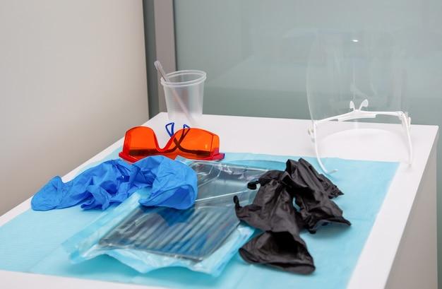Instrumentos médicos esterilizados em embalagem e luvas descartáveis azuis e pretas em um consultório médico