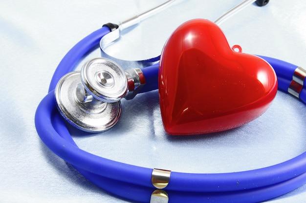Instrumentos médicos, estetoscópio e close up vermelho do coração.