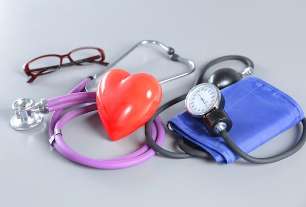 Instrumentos médicos, estetoscópio e coração vermelho para otorrinolaringologia