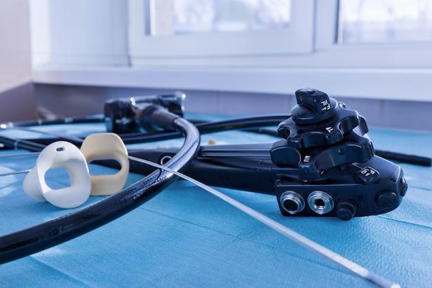 Instrumentos médicos gastroscopia endoscópio close up em uma superfície azul
