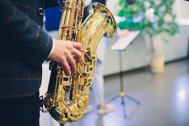 Instrumentos musicais, saxofonista mãos saxofonista tocando música jazz. closeup de instrumento musical de sax alto.