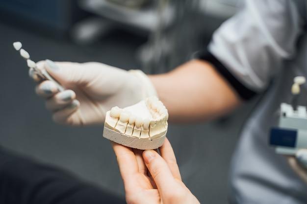 Instrumentos odontológicos e modelo de mandíbula dentária