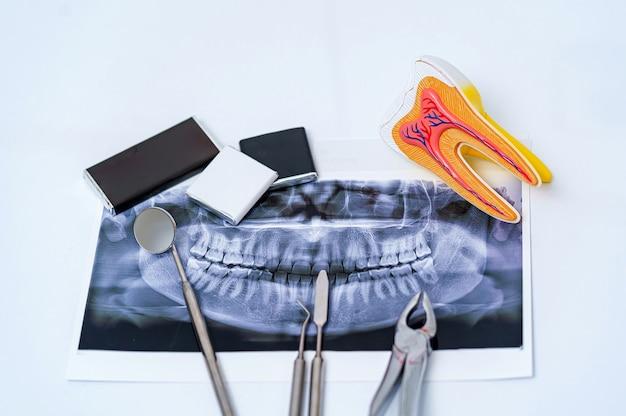Instrumentos odontológicos e raio-x de mandíbula em fundo branco. raio-x panorâmico da mandíbula em fundo branco.